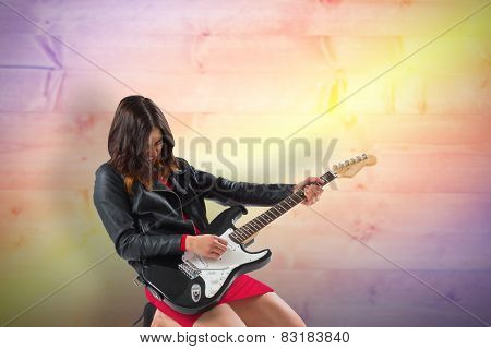 Brunette in biker jacket playing guitar against yellow and purple planks