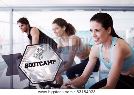 The word bootcamp and fit people in a spin class against hexagon