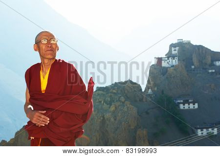 Indian tibetan old monk lama in red color clothing in front of mountain with monastery
