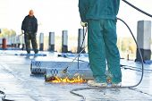 Roofer installing Roofing felt with heating and melting of bitumen roll by torch on flame during roof repair poster