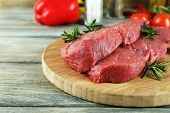 Raw beef steak on cutting board with vegetables and spices on wooden background poster