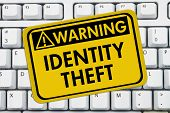 Identity Theft Warning Sign A yellow sign with the words Identity Theft on a keyboard poster
