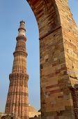 Qutub Minar tower seen through arch Qutub Minar complex Delhi India poster