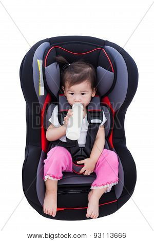 Image of little asian (thai) girl suck up milk and fastened with security belt in safety car-seat Isolated on white background. Concept about the safety of traveling by car children and baby poster