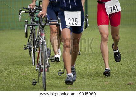 athlete pushing his bike