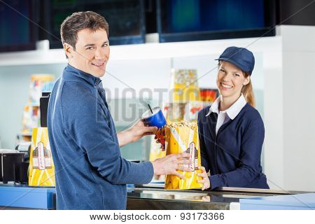 Portrait of smiling man buying popcorn and drink from seller at cinema concession stand