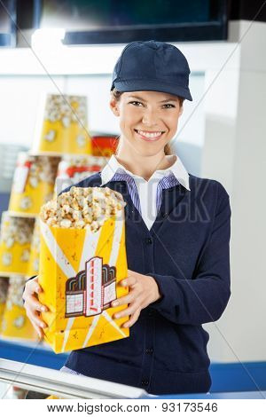 Portrait of confident female worker holding popcorn paperbag at cinema concession stand