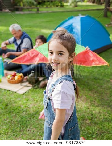 Portrait of cute girl with family relaxing in background at campsite