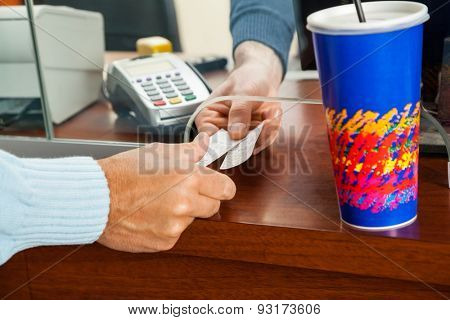 Cropped image of man buying movie tickets from seller at box office