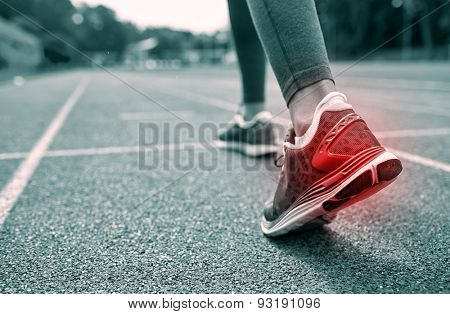 fitness, sport, sports injury, pain and people concept - monochrome close up of woman feet or legs running on track with red spot from back