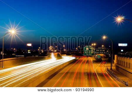 Photo of Rochester Minnesota Highway 52 Near Mayo clinic, View of a highway and city scape at night with light trails taken with a slow shutter speed. poster