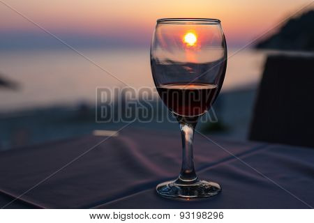 Sunset On Beach Reflected In Glass With Red Wine , Summertime Vacation Concept