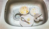 Kitchen conceptual image. Dirty sink with many dirty dishes and kitchenware. poster