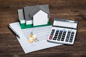 House Model On Contract Paper With Keys And Calculator Kept On Wooden Desk poster