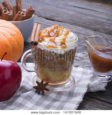 Quick breakfast snack for a few minutes in the microwave. Traditional apple pie in a mug with whipped cream quickly caramel sauce in a transparent mug on a high wooden gray background. selective focus