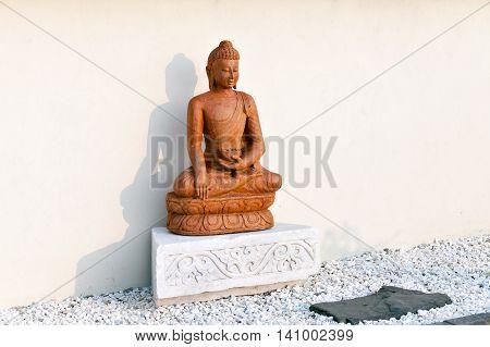 Buddha statue in the setting sun in the garden of stones in the territory of a Buddhist temple. Datsan Rinpoche Bagsha on Bald Mountain in Ulan-Ude, Buryatia, Russia.