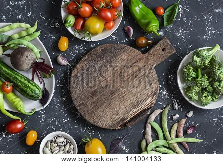 Food background. Assortment of fresh vegetables around the cutting board on a dark background. Top view free space for text
