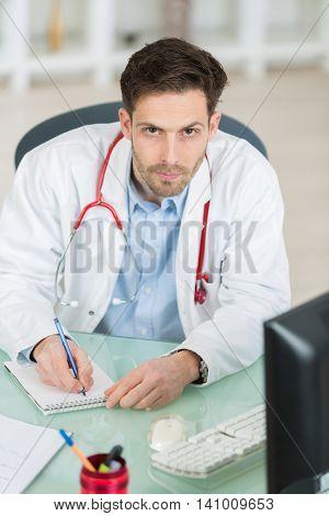 portrait of an handsome doctor writing prescription for patient