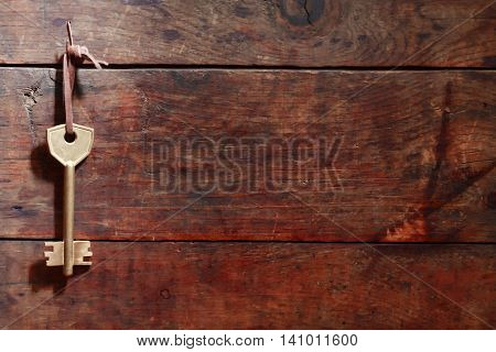 Door key hanging on nice old wooden wall