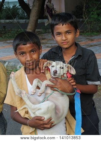 Pune, India - October 07, 2015: Two Indian boys with their pet dogTwo Indian boys with their pet dog