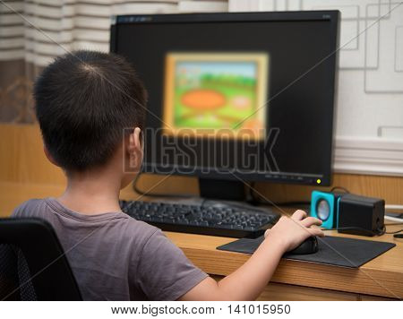 kid playing a computer game for children at home