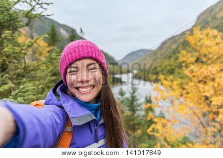Selfie Asian girl hiking in autumn nature mountains. Happy hiker woman taking smartphone picture holding phone at scenic viewpoint in fall mountain landscape outdoors. Forest park travel lifestyle.