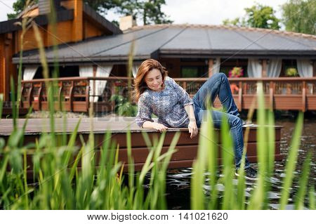 Young woman resting and having fun in the park sitting on a pier over the lake