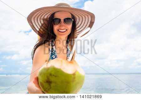 Woman in beachwear and sunglasses holding freshly opened coconut at tropical beach
