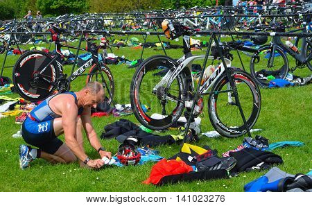 GRAFHAM, CAMBRIDGESHIRE, ENGLAND - MAY 22, 2016:  Male triathlete at end of cycling stage sitting on the ground with bicycles.