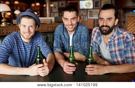 people, leisure, friendship and bachelor party concept - happy male friends drinking bottled beer at bar or pub
