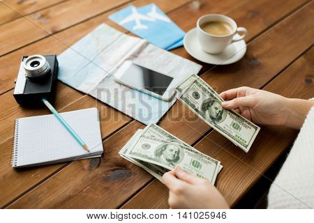 vacation, tourism, travel, finances and people concept - close up of traveler hands counting dollar cash money