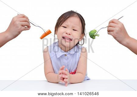 little girl crying because don't want to eat vegetables