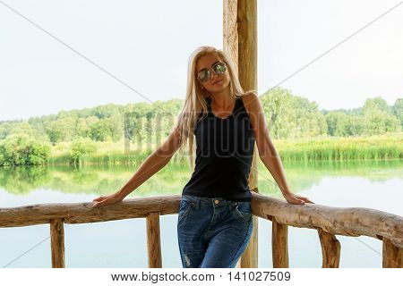 Girl standing on the porch by the lake. Camping wooden fence and porch lake and forest. Summer day.