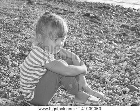 Sad child sitting on stones. Black and white image