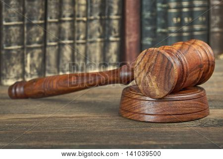 Auctioneer Or Judges Hammer Among Old Books On Wooden Bench