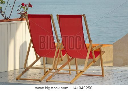 Two Empty Wooden Folding Red Armchair On The Sea View Beach Patio White Floor Near Parapet And Leading Down Staircase