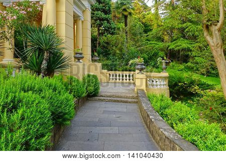Summer Landscape In Tropical Ornamental Park With Walkway And Porch