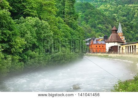 """Embankment Of A Mountain River With Vintage Street Lamp Post And Theme Park """"My Russia"""" Russia Rosa Khutor Alpine Resort poster"""