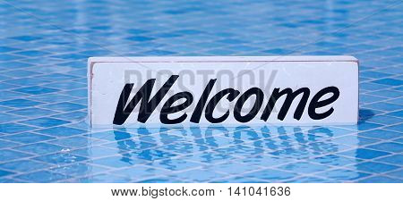 Welcome Sign On White Board In Swimming Pool Water  Surface