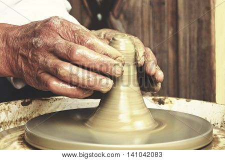 Close Up Of  Mature Potter Hands At Work