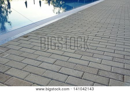 The Edge Of Swimming Pool With Calm Blue Crystal Clear Water And Concrete Paving Floor In Perspective View. Summer Evening Time.