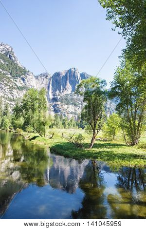 Merced River in Yosemite National Park with Yosemite Falls in the distant background
