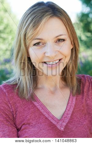 Outdoor Head And Shoulders Portrait Of Smiling Mature Woman