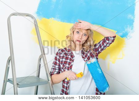 Tired woman at work in the home - painting wall at room. Portrait of woman painting big Ukrainian flag on wall at home.