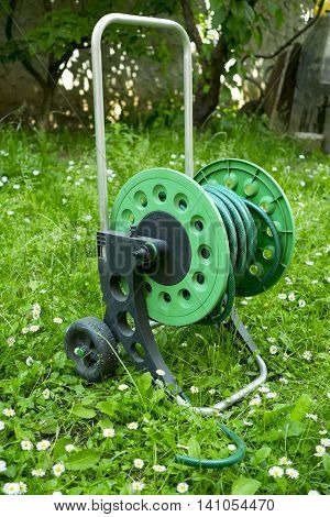 Green garden hose on the spinners with grass in the background