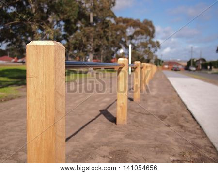 Timber barrier pole and barrier tube bewteen a road and a public park Australia 2016