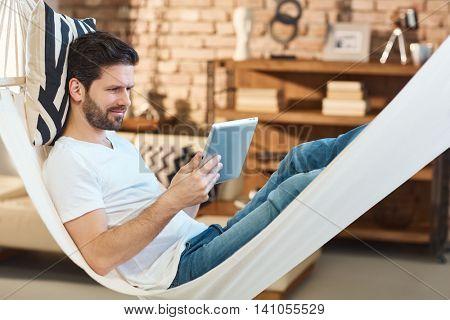 Man using tablet computer resting in hammock.