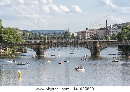 PRAGUE, CZECH REPUBLIC, JULY 5,2016: People having fun with pedalos on Vltava River, Legion Bridge on the background.