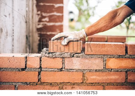 Industrial Bricklayer Worker Placing Bricks On Cement While Building Exterior Walls, Industry Detail