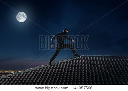 Thief dressed in black walking on the roof of a house